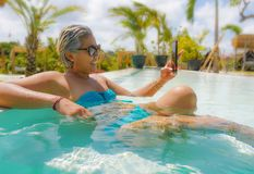 Attractive and happy Asian Indonesian middle aged 40s or 50s woman in bikini at tropical resort swimming pool taking selfie royalty free stock images