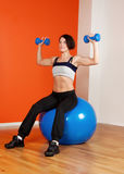 Attractive happy athlete sitting on fitness ball. Portrait of happy brunette sitting on fitness ball with dumbbells Royalty Free Stock Image