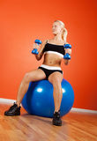 Attractive happy athlete sitting on fitness ball. Beautiful happy blond athlete sitting on fitness ball with dumbbells in gym room Stock Images