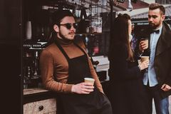 Attractive barista in sunglasses took a coffeebreak at his own coffeeshop. Attractive happy barista in sunglasses took a coffeebreak at his own coffeeshop stock photos