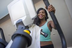 Attractive and happy black African American woman training at fitness club smiling cheerful and sweaty during elliptical machine h Stock Photo