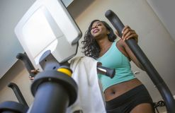 Attractive and happy black African American woman training at fitness club smiling cheerful and sweaty during elliptical machine h Royalty Free Stock Image