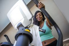Attractive and happy black African American woman training at fitness club smiling cheerful and sweaty during elliptical machine h Stock Photos
