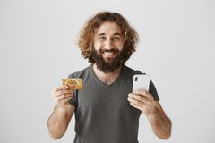 Attractive and happy businessman paying for his delivery with help of internet banking. Portrait of pleased eastern royalty free stock image