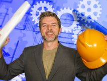 Attractive happy and confident industrial engineer man holding builder helmet and building construction blueprints  on. Development and technology background in stock images