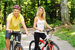 Attractive happy couple on a bicycles in a countryside Stock Photo