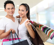 Attractive happy couple carrying shopping bag. Young attractive happy couple at shopping mall Stock Images