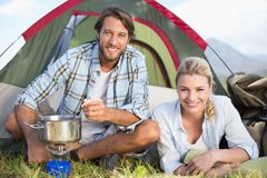 Attractive happy couple cooking on camping stove Royalty Free Stock Photo