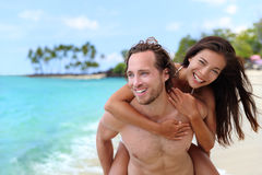 Attractive happy couple laughing having beach fun. Attractive happy couple laughing having fun piggybacking on tropical beach. Caucasian men carrying Asian royalty free stock photography