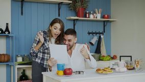 Attractive happy couple recieve good news unfolding letter in the kitchen while have breakfast at home. Early morning Stock Image