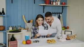 Attractive happy couple recieve good news unfolding letter in the kitchen while have breakfast at home. Early morning Stock Images