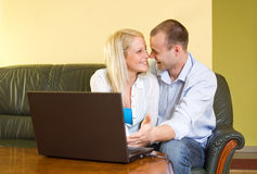 Attractive happy couple using laptop at home. Royalty Free Stock Photography