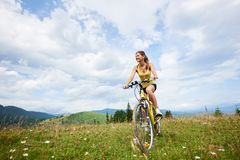 Attractive female cyclist with yellow mountain bicycle, enjoying sunny day in the mountains. Attractive happy female cyclist riding on yellow mountain bike on a royalty free stock photos