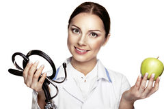 Attractive happy female doctor holding green apple and stethosco Royalty Free Stock Photo