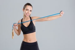 Attractive happy fitness girl warming up with jumping rope Stock Image