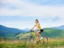 Attractive female cyclist with yellow mountain bicycle, enjoying sunny day in the mountains. Attractive happy girl cyclist riding on yellow mountain bike on a stock image