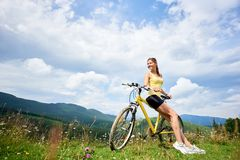 Attractive female cyclist with yellow mountain bicycle, enjoying sunny day in the mountains. Attractive happy girl cyclist sitting on yellow mountain bike royalty free stock photography
