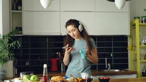 Attractive happy girl dancing and singing in kitchen while using smartphone and listening to music at home in the. Cheerful happy girl dancing and singing in stock footage
