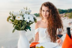 Attractive happy girl with glass on wine on romantic date. On beach stock photos
