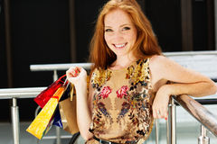 Attractive happy girl out shopping. Attractive happy teenager smiling girl with colorful shopping bags Royalty Free Stock Image