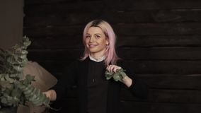 An attractive, happy girl with pink hair removes a handful of green leaves from a branch and playfully throw at the. Camera stock video footage