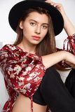 Attractive happy girl is possing and smilling in flower red dress and black hat on white stock photography