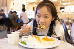 Attractive happy girl sitting and eating dessert,Close up portrait of a hungry greedy girl eating panckaces in the restaurant royalty free stock image