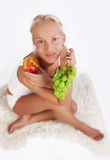 Attractive happy girl sitting on fell with fruits Royalty Free Stock Photo