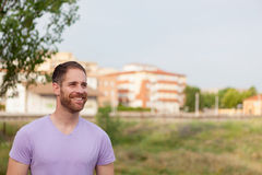 Attractive happy guy with beard and purple tshirt stock images