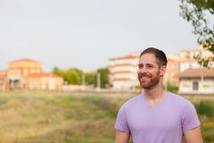 Attractive happy guy with beard and purple tshirt stock photography