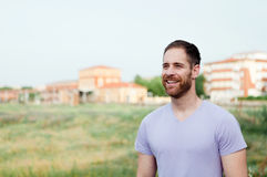 Attractive happy guy with beard and purple tshirt royalty free stock photos