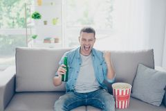 Attractive, happy guy watching football, celebrating victory of. His favorite team with raised fist, yelling,  having beer and pop corn, sitting in living room Royalty Free Stock Photos