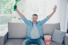 Attractive, happy guy watching football, celebrating victory of. Sport rate with raised hands, yelling, won a lot of money, having beer and pop corn, sitting in Stock Photo