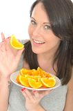 Attractive Happy Healthy Natural Young Woman Holding a Plate of Ripe Juicy Orange Segments. A DSLR royalty free image, a happy attractive natural healthy young Royalty Free Stock Photos