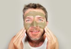 Attractive and happy man looking to himself in bathroom mirror with green cream on his face applying facial mask skin care product. Lifestyle isolated portrait Royalty Free Stock Images