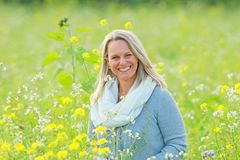 Happy mature woman  in a flowerfield Royalty Free Stock Image