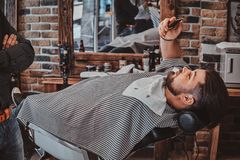 Thendy hairdresser at modern barbershop is working on client`s haircut. Attractive happy men is chatting bu smartphone while waiting for his barber stock image