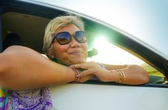 Attractive and happy middle aged Asian Indonesian woman 40s or 50s  with grey hair and beautiful smile sitting in her car enjoying stock photo