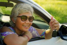 Attractive and happy middle aged Asian Indonesian woman 40s or 50s  with grey hair and beautiful smile sitting in her new car stock photos