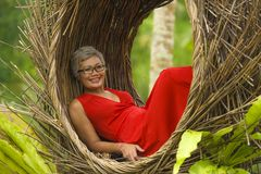 Attractive and happy middle aged 40s or 50s Asian tourist woman with grey hair and elegant red dress sitting outdoors at tropical. Natural lifestyle portrait of royalty free stock images
