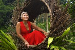 Attractive and happy middle aged 40s or 50s Asian tourist woman with grey hair and elegant red dress sitting outdoors at tropical. Natural lifestyle portrait of royalty free stock photo