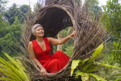 Attractive and happy middle aged 40s or 50s Asian tourist woman with grey hair and elegant red dress sitting outdoors at tropical. Natural lifestyle portrait of royalty free stock photography