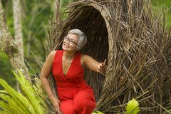 Attractive and happy middle aged 40s or 50s Asian tourist woman with grey hair and elegant red dress sitting outdoors at tropical. Natural lifestyle portrait of stock image