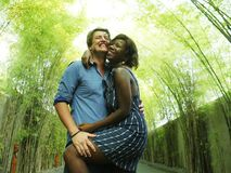 Attractive and happy mixed ethnicity couple cuddling with attractive black afro American girlfriend or wife and handsome Caucasian. Young attractive and happy stock image