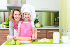 Attractive happy mother and daughter baking. Attractive happy mother and daughter baking together at the kitchen Royalty Free Stock Photo