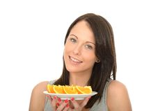 Attractive Happy Natural Young Woman Holding a Plate of Ripe Juicy Orange Segments. A DSLR royalty free image, a happy attractive natural young woman, holding a Royalty Free Stock Photos