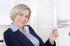 Attractive happy older or senior business woman in the office. Royalty Free Stock Images