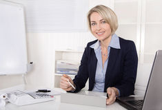 Attractive happy older or senior business woman in the office. Stock Photo
