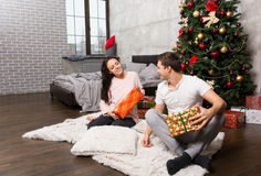 Attractive happy pair in pajamas rejoice at their presents while Stock Image