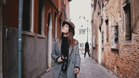 Attractive happy professional female photographer walking with camera smiling along beautiful old street in Venice Italy. Successful freelance Caucasian stock video footage